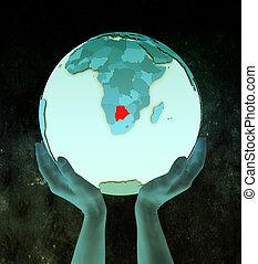 Botswana on blue globe in hands
