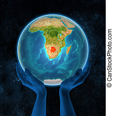 Botswana on Earth in hands in space