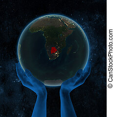 Botswana on night Earth in hands in space