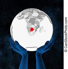 Botswana on white globe in hands