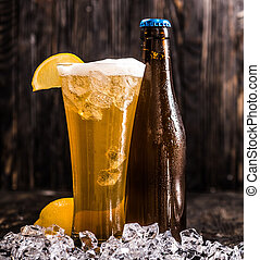 bottle and a glass of beer with ice and lemon