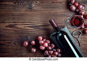 Bottle and glass of red wine and grapes on wooden background...