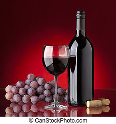 Bottle and glass of red wine, grape and cork on a red ...