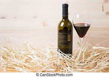 Bottle and glass of red wine in str