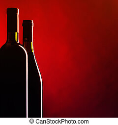Bottle and glass of red wine on dark red background....