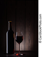 Bottle and glass of red wine on wooden background