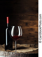 Bottle and glass of red wine on wooden barrel shot with dark wooden background. creative photo.