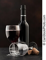 Bottle and glass of red wine with corks on dark.
