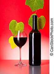 Bottle and glass of red wine with grape leaves