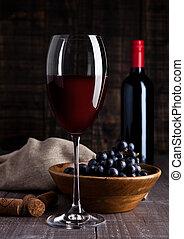 Bottle and glass of red wine with grapes in bowl