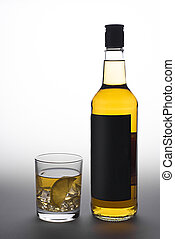 Bottle and glass of whiskey with ice on a white-gray background