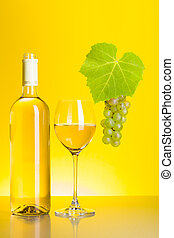 Bottle and glass of white wine with grape cluster