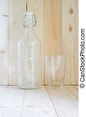 Bottle and glass on wooden table with mornig sunshine