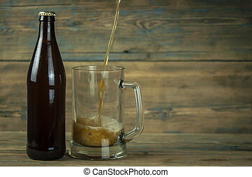 bottle and glass with beer on wood table
