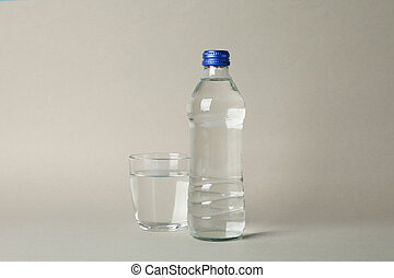 Bottle and glass with water on gray background, space for text