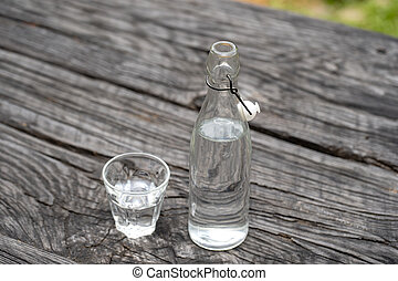Bottle and glass with water on the wooden table