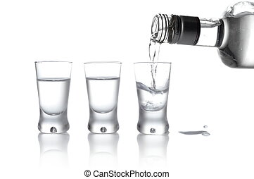 Bottle and glasses of vodka poured into a glass isolated on ...