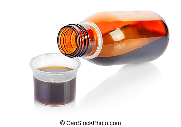 Bottle and plastic measuring cup of syrup medication on...