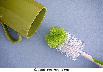 Bottle brush and green mug. Blue background.