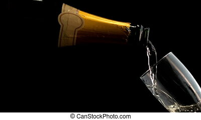 Bottle filling champagne flute against black background