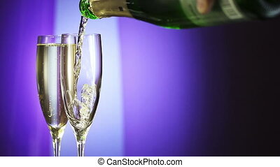 Bottle filling champagne flute against blue background. slow...