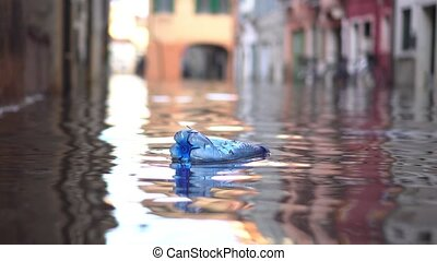 Bottle floats on the water of the flooded city