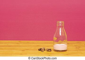 Bottle half full of strawberry milkshake with cookie crumbs