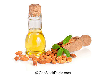 Bottle of almond oil and almonds with leaf in a wooden scoop isolated on white background