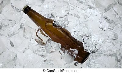 Bottle of beer in the ice, it pulls out a man's hand. White background. Slow motion