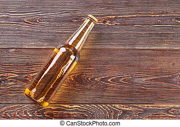 Bottle of beer lying on wooden table.