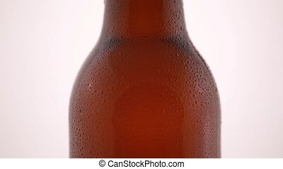 Bottle of beer with drops isolated on white background