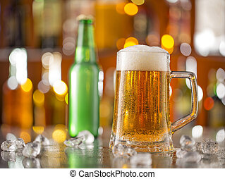 Bottle of beer with glass on bar desk