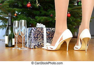 Bottle of champagne and a gift under the Christmas tree