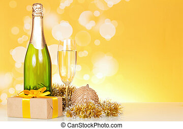 Bottle of champagne in holiday setting with gift