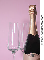bottle of champagne with glasses on a pink background