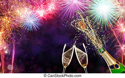 Bottle of champagne with glasses over fireworks background -...