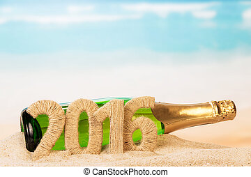 Bottle of champagne with inscription 2016 on sand