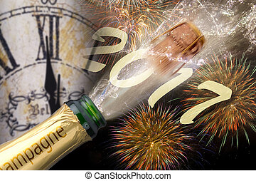 bottle of champagne with popping cork at new years 2017 in...