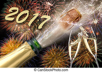 bottle of champagne with popping cork at new years 2017