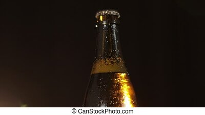 Bottle of cold beer on a black background. It slowly rotates. Condensate