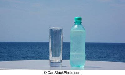 bottle of cold water and glass standing on table, sea in ...