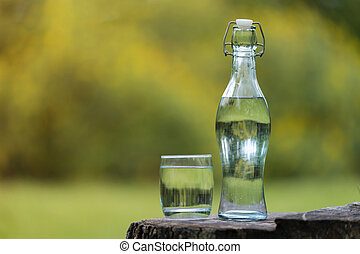 Bottle of Drink water and glass with natural background