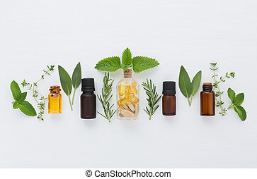 Bottle of essential oil and herbal medicine with fresh herbs sage, rosemary, thyme, mint, lemon balm and spearmint setup with flat lay on white wooden table. top view
