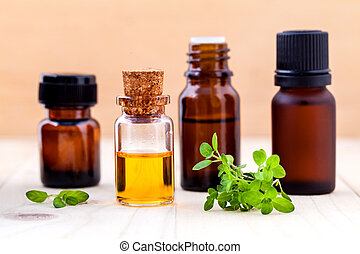 Bottle of essential oil and lemon thyme  leaf  on wooden background.