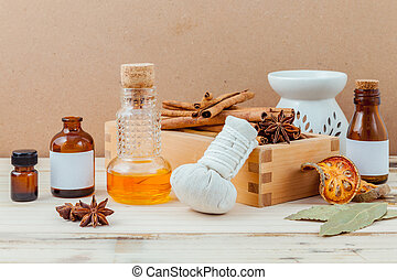 Bottle of essential oil with cinnamon stick ,star anise ,bay leaves with selective focus on old wooden background .