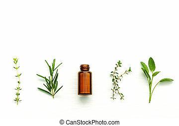 Bottle of essential oil with fresh herbal sage, rosemary, ...