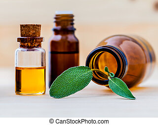 Bottle of essential oil with  fresh sage leaves shallow depth of field on old wooden background.