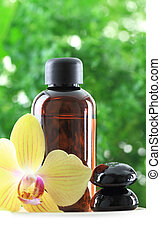 Bottle of essential oil with orchid flower and zen stones