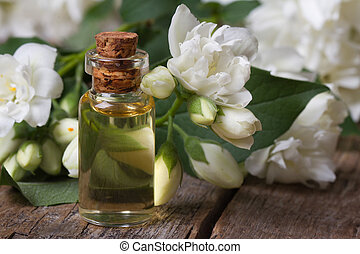 bottle of fragrant jasmine essence closeup and flowers