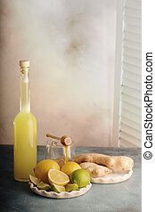 Bottle of homemade juice with ginger and lemon on light background.